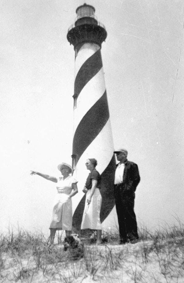 Marjory Stoneman Douglas standing in front of a black-and-white striped lighthouse. She is pointing at something off camera left.