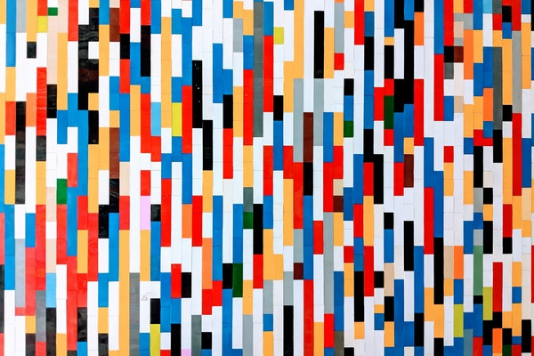a wall of differently colored legos making a pattern of lines