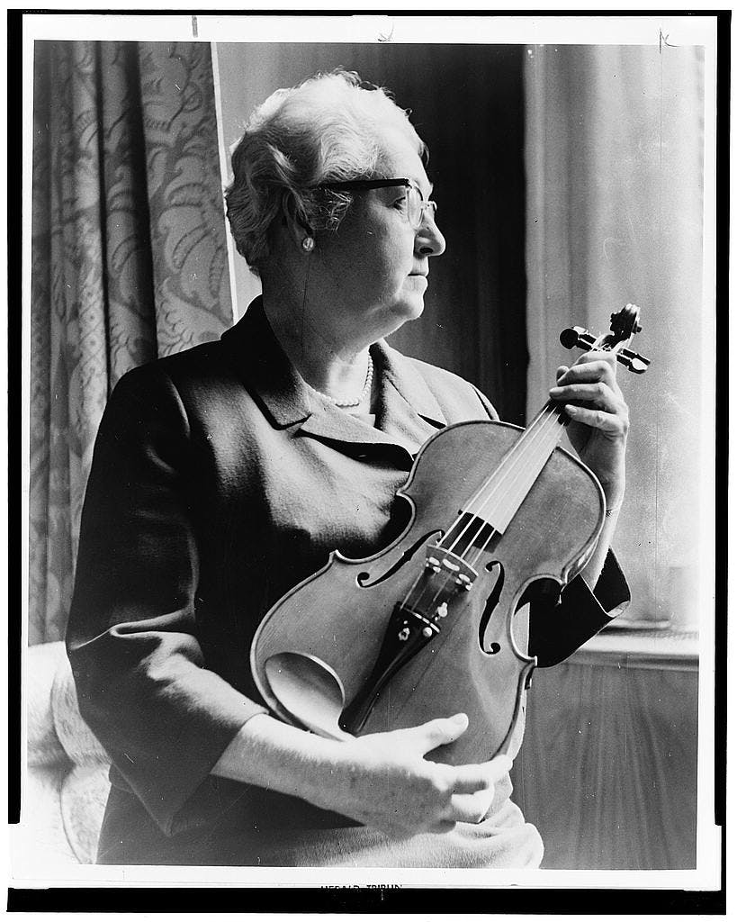 "Apgar, a musician as well, examining a violin ""fashioned from an old telephone shelf"""