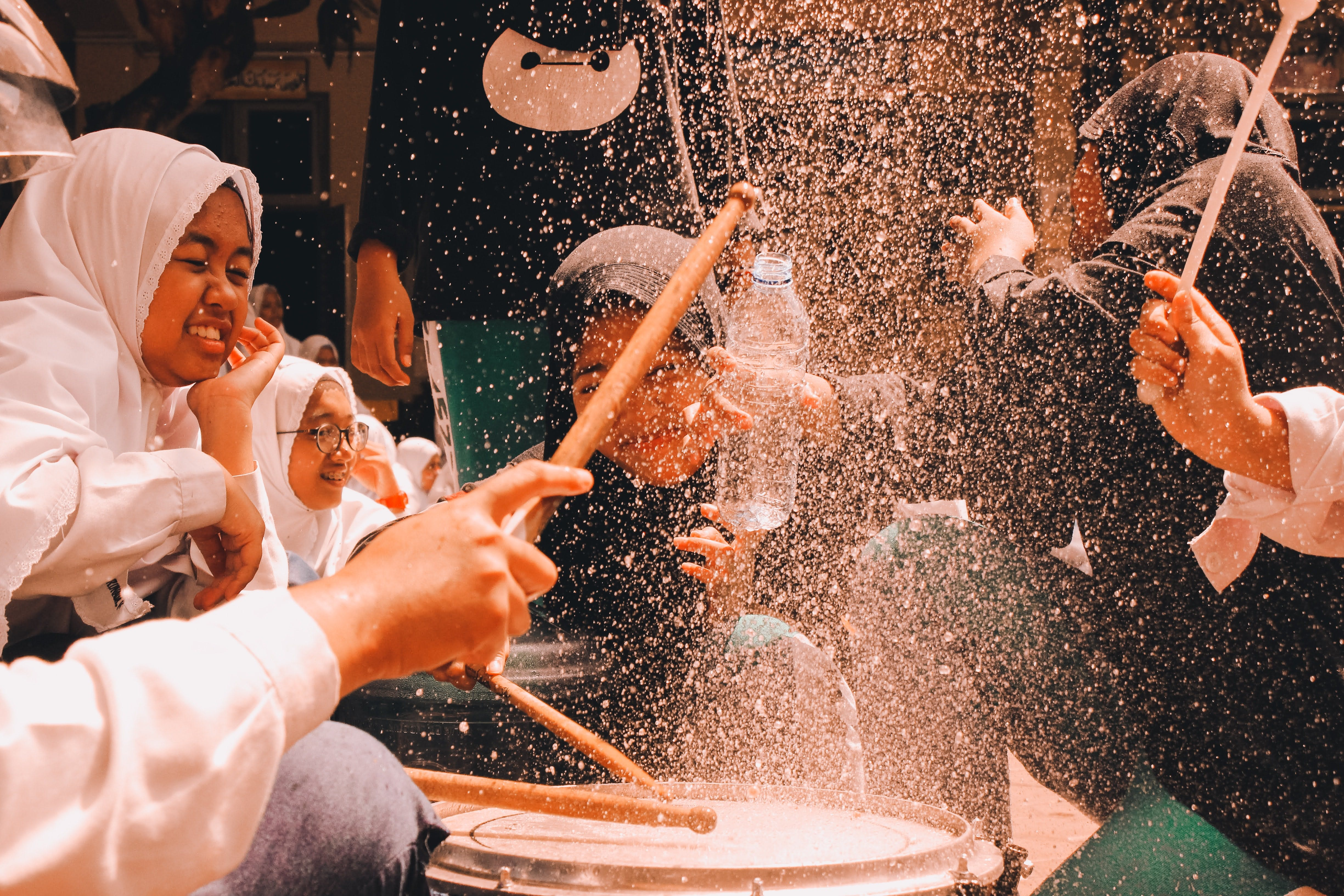 girls in Indonesia playing drums and smiling