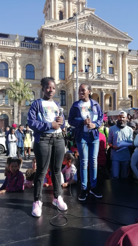 Two climate strikers stand on a stage about to give a speech in Cape Town, South Africa.