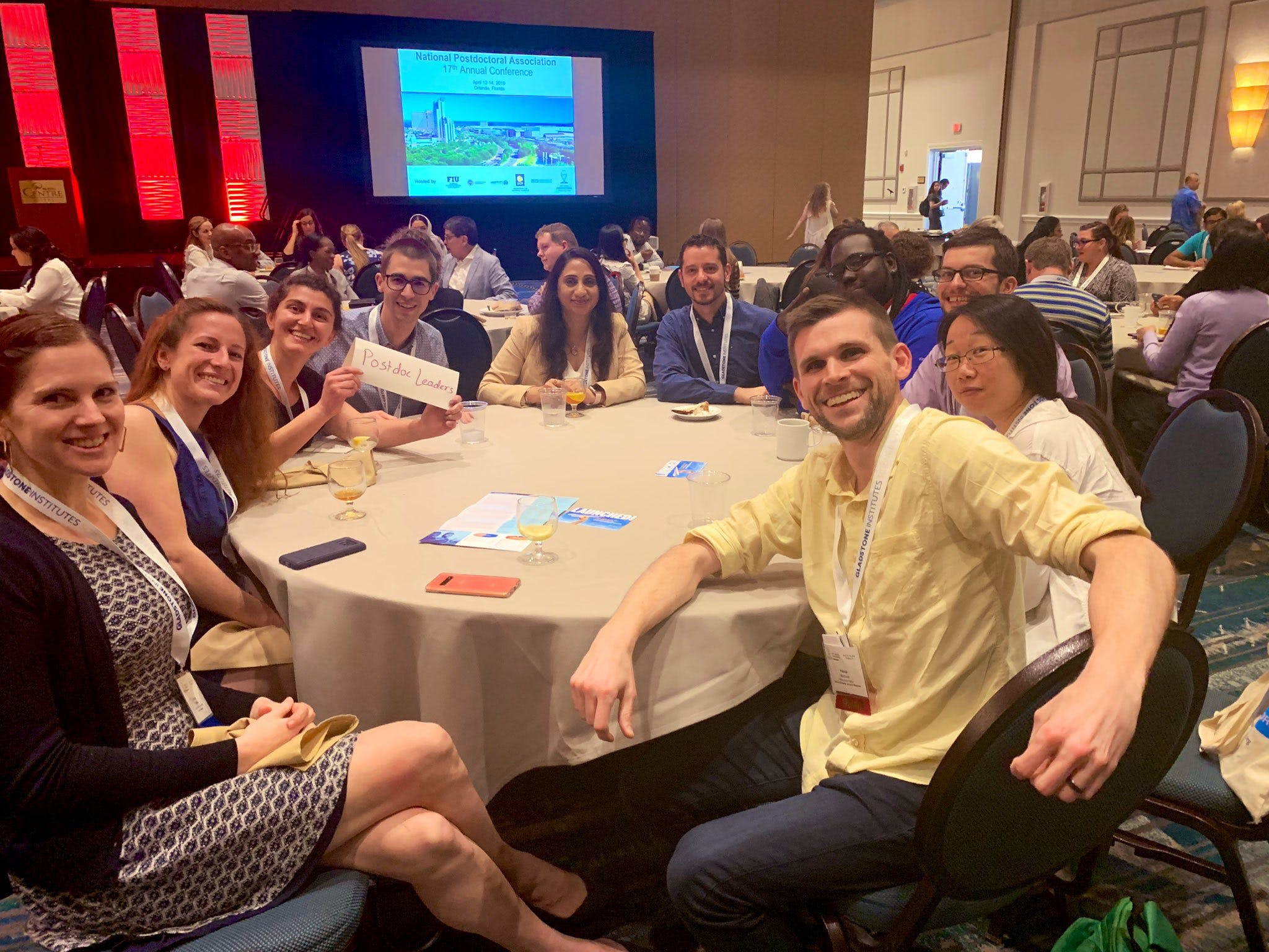 """A group of people posing for a photo seated at a circular table. One is holding a paper sign that reads """"Postdoc Leaders."""""""