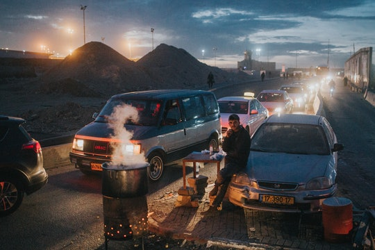 A man waiting by lines of cars going through a checkpoint from Ramallah, Palestine to enter Israel.