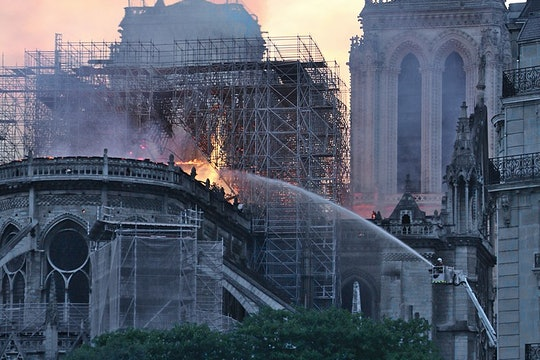 firefighter spraying water on the burned notre dame cathedral