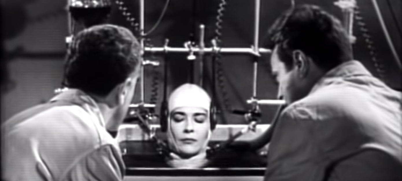 "A still from the movie ""The Brain That Wouldn't Die"", 1962. Two scientists contemplate a woman's head kept alive in a lab."