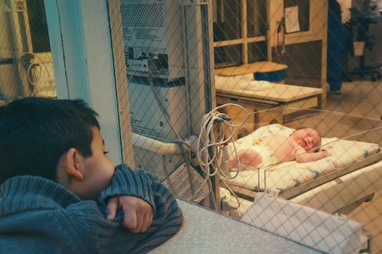 A child looks through a glass window at a newborn in a bassinet