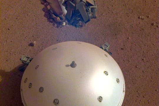 A white dome covers the seismometer from NASA's InSight rover, on the surface of Mars.