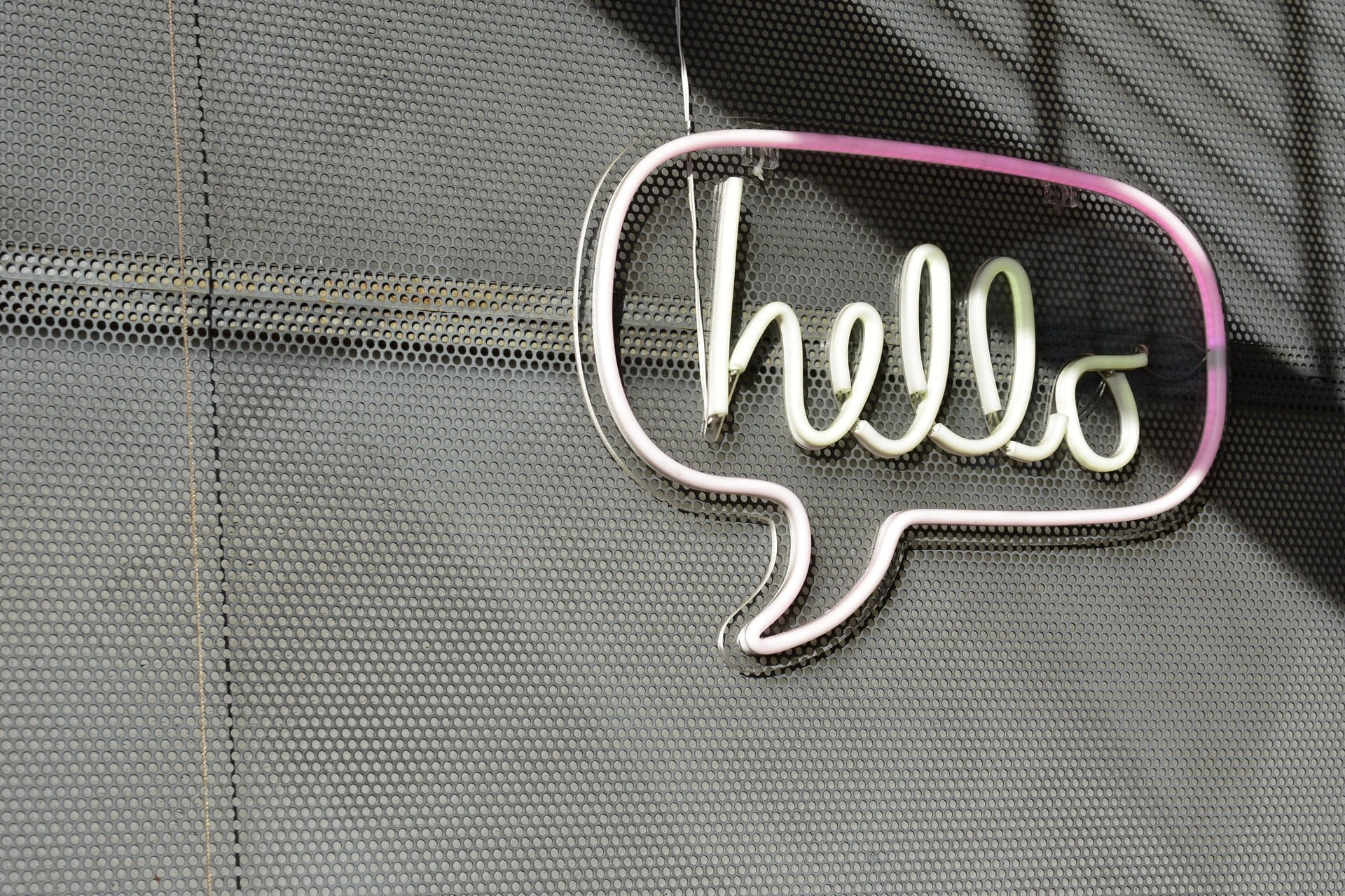 "A neon sign in the shape of a speech bubble that says ""hello"""