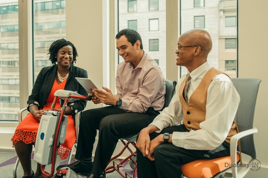 three disabled people with various accommodations working together