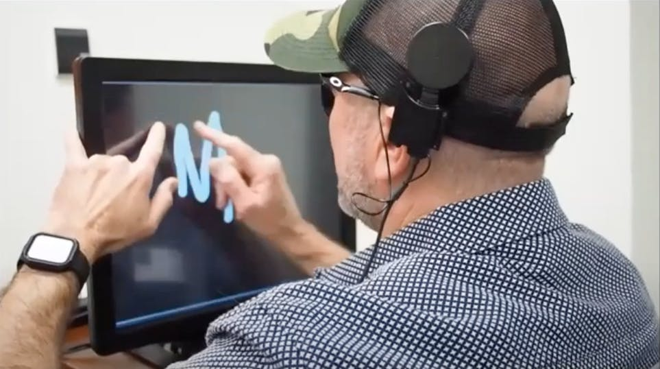 A man traces a shape, stimulated in his mind, on a computer screen with his finger