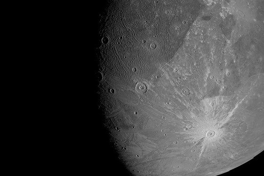 a detailed image of a large moon with round pockmarks on the surface
